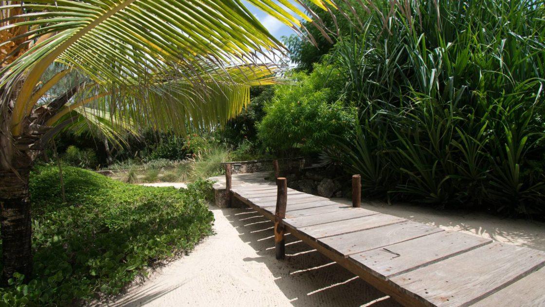 Wooden bridge on sandy garden