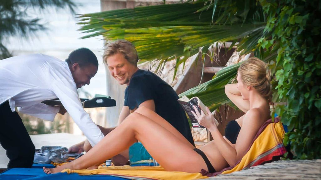 Allan serving guests on sunbeds at the swimming pool
