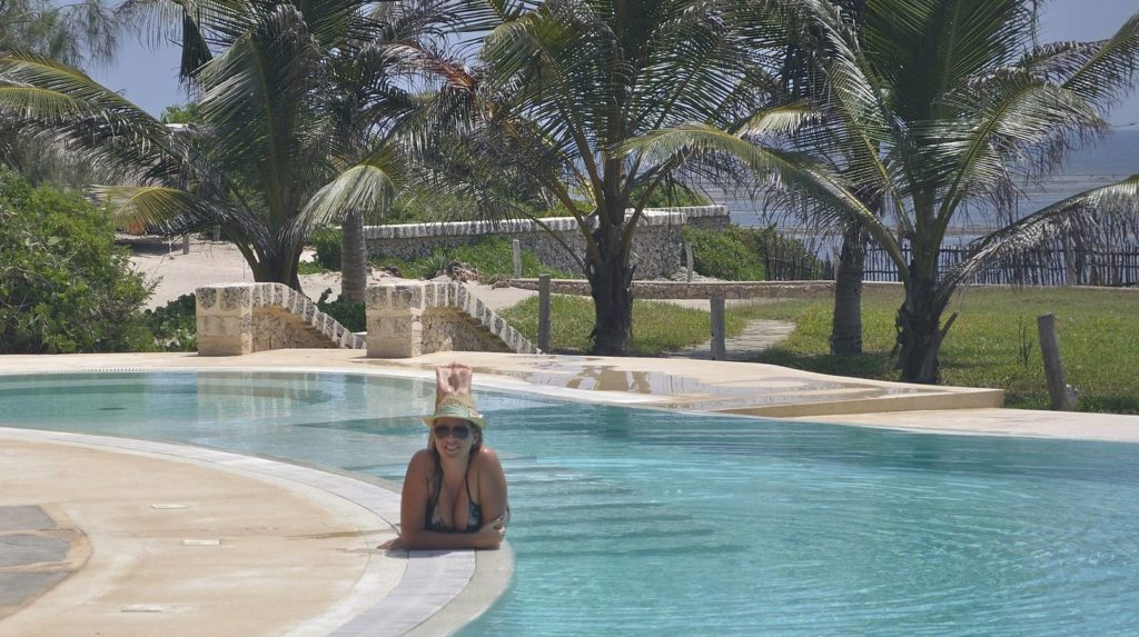 Guest with hat tanning beside lonno lodge swimmingpool