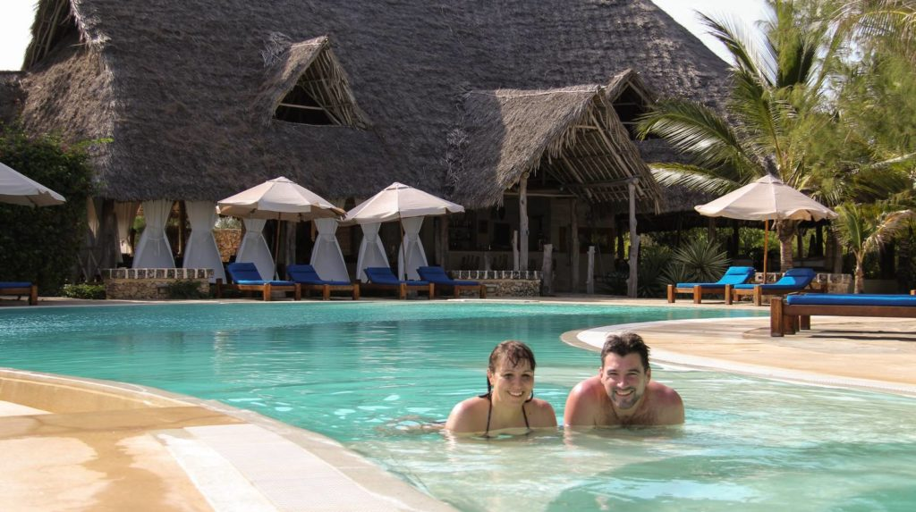 Guests in swimming pool with restaurant on the background