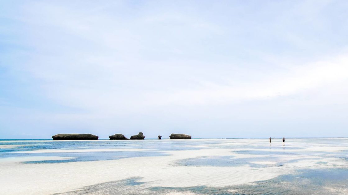 Two guests walking at low tide on a solitary beach
